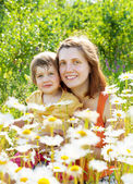 Mother with daughter in camomile plant — Photo