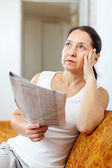 Serious and wistful woman with newspaper — Stock Photo