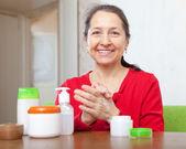 Mature woman applying cream on hands — Stock Photo