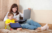 Woman with toddler using laptops — Stockfoto