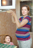 Pregnant woman warms up food — Stok fotoğraf