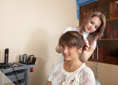 Female hair stylist working with long-haired girl — Stock Photo