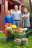 Happy family with vegetables in garden — Stock Photo