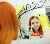 Teenager cleans mirror with sponge — Stock Photo