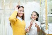 Saleswoman helps bride chooses bridal diadem — Stock Photo