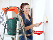 Happy girl in overalls paints wall — Stock Photo