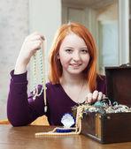 Mädchen wählt Halskette in Schatztruhe — Stockfoto