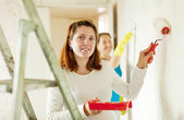 Women paints wall at house — Stock Photo