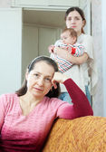 Mature woman and daughter with baby having quarre — Stock Photo