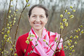 Mature woman in spring pussywillow plant — Stock Photo