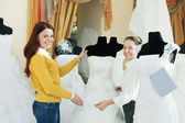 Woman helps girl chooses white bridal outfit — Stock Photo