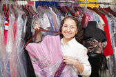 Female buyer chooses evening dress — Stock Photo