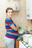 Pregnant woman washing dishes — Stock fotografie