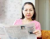 Serious woman reading newspaper — Stock Photo