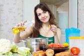 Schöne hausfrau kochen gemüse mit öl — Stockfoto