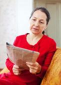 Wistful woman reading newspaper — Stock Photo