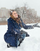 Young woman throwing snow in air — Stock Photo