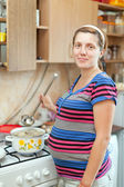 Pregnant woman cooking food — Stock fotografie