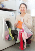 Mature woman loading the washing machine — Stockfoto