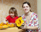 Woman with child cooks pumpkin — Stock Photo