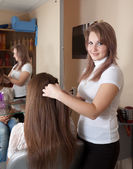 Hairdresser works on woman hair — Stock Photo