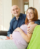 Happy pregnant couple in home — Stok fotoğraf