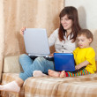 Happy woman with toddler using laptops in living room — Stock Photo