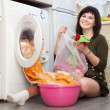 Stock Photo: Housewife loading washing machine