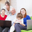 Family uses few various portable devices in home interior — Stock Photo