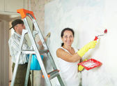Smiling mature woman and man making repairs — Stock Photo