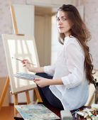 Long-haired woman with oil colors near easel — Stock Photo