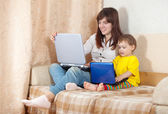 Happy woman with toddler using laptops in living room — Stockfoto