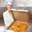 Female cook with pizza in box — Stock Photo