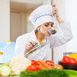 Cook in white uniform tests soup from ladle — Stock Photo #27490715