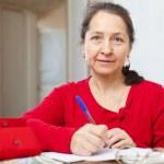 Serious mature woman fills bills — Stock Photo