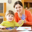 Happy mother and child painting on paper — Stock Photo