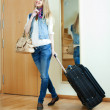 Stock Photo: Happy girl with luggage near door
