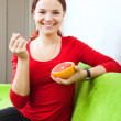 Young woman eats grapefruit with spoon — Stock Photo