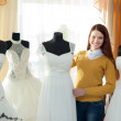 Smiling woman chooses  wedding dress — Stockfoto