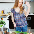 Stock Photo: Positive housewife cooking saltwater fish