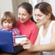 Happy family paying by credit card in internet store — Stok Fotoğraf #27491821