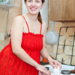 woman in red cleans gas stove with melamine sponge   — ストック写真