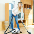 Stock Photo: Blonde womin headphones cleaning with vacuum cleaner