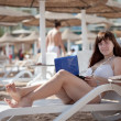 Stock Photo: Womusing laptop at resort beach