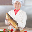 Stock Photo: Cook womis cooking fish
