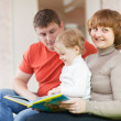 Happy parents with child looks the book — Stock Photo #27492483