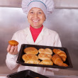 Baker with fresh pastries — Stock Photo