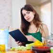 Beautiful woman reads cookbook for recipe — ストック写真