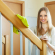 Stock Photo: Womcleaning wooden stair railings at home