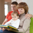 Parents with child looks the book — Stock Photo #27492953